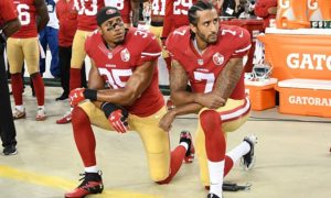 Colin Kaepernick (right) and Eric Reid of the San Francisco 49ers kneel in protest. Photo via CNN