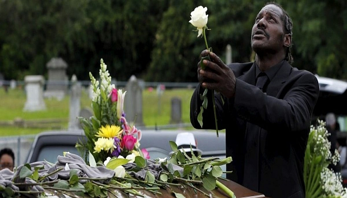 Gary Washington stands over the casket of his mother, Ethel Lance, as she is buried at the Emanuel African Methodist Episcopal Church cemetery in North Charleston, South Carolina June 25, 2015. REUTERS/Brian Snyder