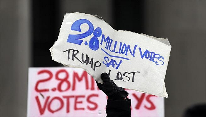 Protesters hold signs outside the Capitol before Electoral College electors begin voting Monday in Olympia, Wash. (AP Photo/Elaine Thompson)