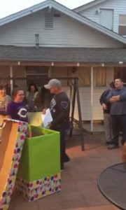 Man's stepdaughter emerges from giant birthday box with surprise in her hand - photo credit - Shareably