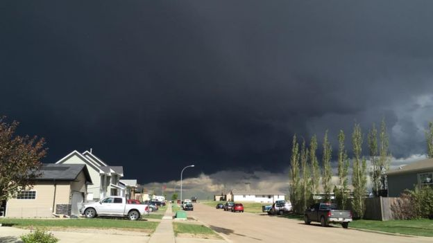 Photo Of Canada Man Mowing Lawn With Tornado Behind Him Goes Viral